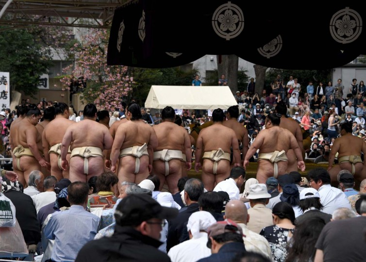 "Sumo wrestlers line up to take part in a ""honozumo,"" a ceremonial sumo exhibition, on the grounds of Yasukuni Shrine in Tokyo on April 17, 2017. Sumo's top wrestlers took part in an annual one-day exhibition for thousands of spectators within the shrine's precincts. (TOSHIFUMI KITAMURA/AFP/Getty Images)"