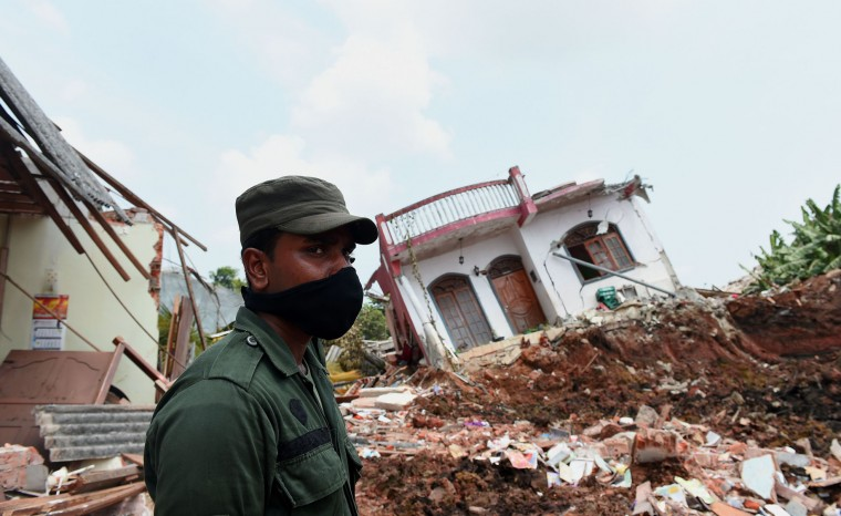 A Sri Lankan military official stands among damaged homes at the site of a collapsed garbage dump in Colombo on April 18, 2017. Hundreds of tonnes of rotting garbage piled up in Sri Lanka's capital on April 18 after the main rubbish dump was shut following an accident that killed at least 31 people. Authorities sealed the massive 300-foot (90-metre) rubbish mountain on the northeastern edge of Colombo after it collapsed Friday, destroying 145 homes nearby and burying victims in a garbage landslide. (Ishara S. Kodikara/AFP/Getty Images)