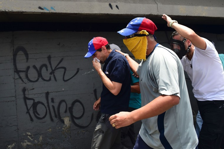 Opposition leader Henrique Capriles (C, wearing cap with Venezuelan colours) looks for refuge under a bridge as police throw tear gas during a rally against Venezuelan President Nicolas Maduro, in the streets of Caracas on April 19, 2017. Venezuela braced for rival demonstrations Wednesday for and against President Nicolas Maduro, whose push to tighten his grip on power has triggered waves of deadly unrest that have escalated the country's political and economic crisis. (Ronaldo Schemidt/AFP/Getty Images)