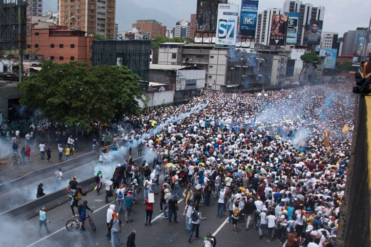 Demonstrators clash with riot police during a march against Venezuelan President Nicolas Maduro, in Caracas on April 19, 2017. Venezuelans took to the streets Wednesday for massive demonstrations for and against President Nicolas Maduro, whose push to tighten his grip on power has triggered deadly unrest that has escalated the country's political and economic crisis. (Carlos Becerra/AFP/Getty Images)