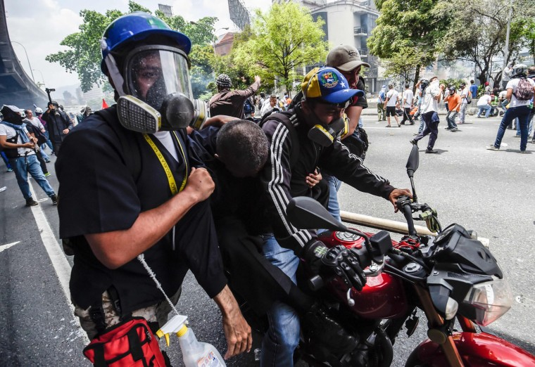 Wounded people are transported after protesters taking part in a rally against the government of President Nicolas Maduro clashed with the riot police in Caracas, on April 19, 2017. Venezuelans took to the streets Wednesday for massive demonstrations for and against President Nicolas Maduro, whose push to tighten his grip on power has triggered deadly unrest that has escalated the country's political and economic crisis. (Juan Barreto/AFP/Getty Images)
