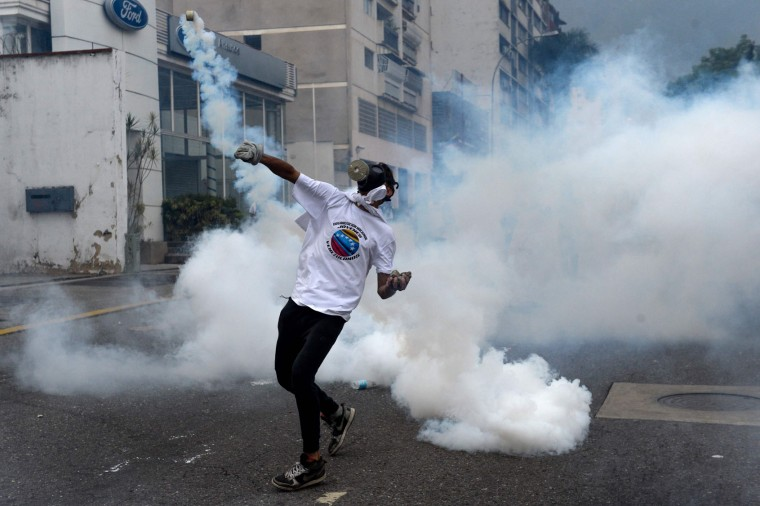 A demonstrator throws back at riot police a tear gas grenade during a march against Venezuelan President Nicolas Maduro, in Caracas on April 19, 2017. Venezuelans took to the streets Wednesday for massive demonstrations for and against President Nicolas Maduro, whose push to tighten his grip on power has triggered deadly unrest that has escalated the country's political and economic crisis. (Federico Parra/AFP/Getty Images)