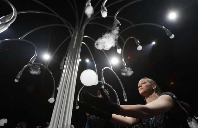 "A woman takes a ball as she visits an installation called ""New Spring"" by Studio Swine for Cos' furniture designers, part of the Design Fair exhibition in Milan, Italy, Thursday, April 6, 2017. It is a multi-sensory installation. (AP Photo/Antonio Calanni)"