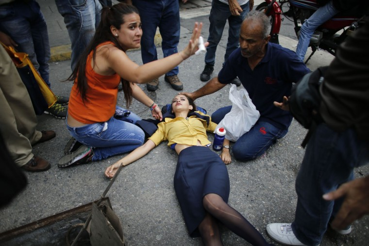 A woman is aided by fellow demonstrators after falling, overcome by tear gas, during anti-government protests in Caracas, Venezuela, Thursday, April 20, 2017. Tens of thousands of protesters asking for the resignation of President Nicolas Maduro flooded the streets again Thursday, one day after three people were killed and hundreds arrested in the biggest anti-government demonstrations in years. (AP Photo/Ariana Cubillos)