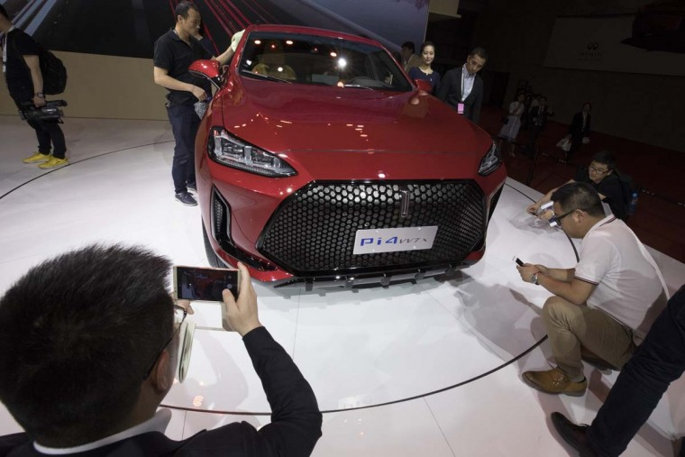 Visitors take photos of the WEY Pi4vv7x concept car from Chinese automaker Great Wall during the Auto Shanghai 2017 show at the National Exhibition and Convention Center in Shanghai, China, Wednesday, April 19, 2017. Models on display at Auto Shanghai 2017, the global industry's biggest marketing event of the year, reflect the conflict between Beijing's ambitions to promote environmentally friendly propulsion and Chinese consumers' love of hulking, fuel-hungry SUVs. (AP Photo/Ng Han Guan)