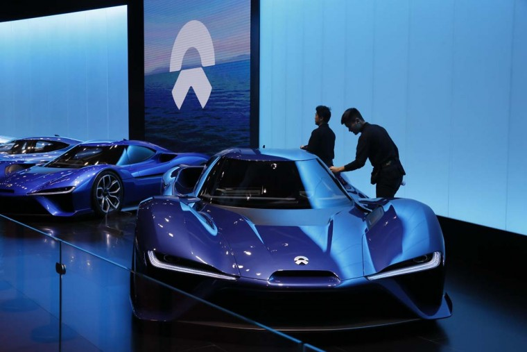Workers attend to sports vehicle from Chinese startup NIO during the Auto Shanghai 2017 show at the National Exhibition and Convention Center in Shanghai, China, Wednesday, April 19, 2017. Models on display at Auto Shanghai 2017, the global industry's biggest marketing event of the year, reflect the conflict between Beijing's ambitions to promote environmentally friendly propulsion and Chinese consumers' love of hulking, fuel-hungry SUVs. (AP Photo/Ng Han Guan)