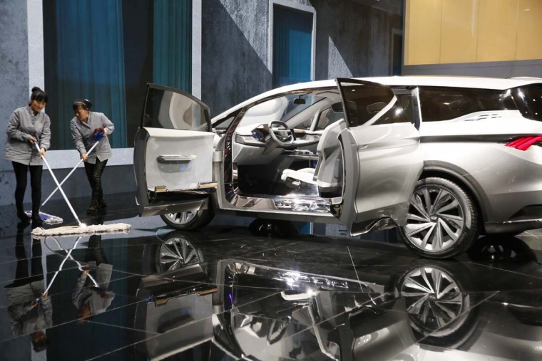 Workers mop the floor near a MPV concept car from Chinese automaker Geely during the Auto Shanghai 2017 show at the National Exhibition and Convention Center in Shanghai, China, Wednesday, April 19, 2017. Models on display at Auto Shanghai 2017, the global industry's biggest marketing event of the year, reflect the conflict between Beijing's ambitions to promote environmentally friendly propulsion and Chinese consumers' love of hulking, fuel-hungry SUVs. (AP Photo/Ng Han Guan)