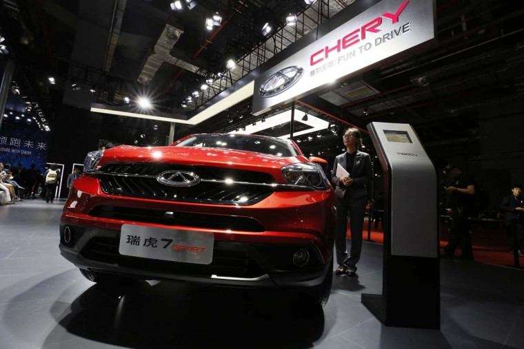 A worker stands near a vehicle at the Chery stand during the Auto Shanghai 2017 show at the National Exhibition and Convention Center in Shanghai, China, Wednesday, April 19, 2017. Models on display at Auto Shanghai 2017, the global industry's biggest marketing event of the year, reflect the conflict between Beijing's ambitions to promote environmentally friendly propulsion and Chinese consumers' love of hulking, fuel-hungry SUVs. (AP Photo/Ng Han Guan)