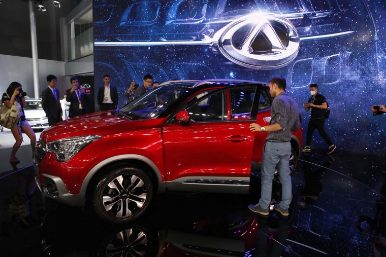 Visitors take a closer look at the Tiggo 5 from Chinese automaker Chery during the Auto Shanghai 2017 show at the National Exhibition and Convention Center in Shanghai, China, Wednesday, April 19, 2017. Models on display at Auto Shanghai 2017, the global industry's biggest marketing event of the year, reflect the conflict between Beijing's ambitions to promote environmentally friendly propulsion and Chinese consumers' love of hulking, fuel-hungry SUVs. (AP Photo/Ng Han Guan)