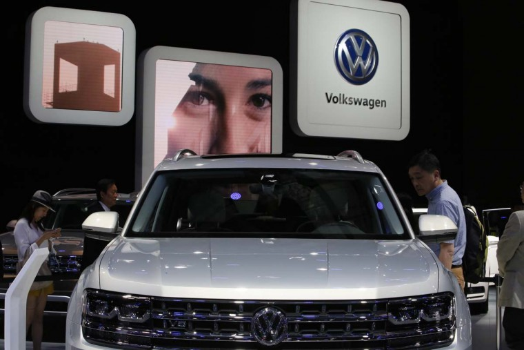 Visitors at the Volkswagen stand during the Auto Shanghai 2017 show at the National Exhibition and Convention Center in Shanghai, China, Wednesday, April 19, 2017. Models on display at Auto Shanghai 2017, the global industry's biggest marketing event of the year, reflect the conflict between Beijing's ambitions to promote environmentally friendly propulsion and Chinese consumers' love of hulking, fuel-hungry SUVs. (AP Photo/Ng Han Guan)