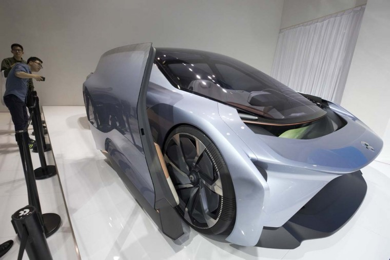 Visitors look at the EVE concept car from Chinese startup NIO during the Auto Shanghai 2017 show at the National Exhibition and Convention Center in Shanghai, China, Wednesday, April 19, 2017. Models on display at Auto Shanghai 2017, the global industry's biggest marketing event of the year, reflect the conflict between Beijing's ambitions to promote environmentally friendly propulsion and Chinese consumers' love of hulking, fuel-hungry SUVs. (AP Photo/Ng Han Guan)