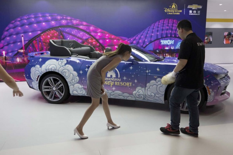 Workers attend to a converted Chevrolet Camaro car in collaboration with Disney displayed at the Auto Shanghai 2017 show at the National Exhibition and Convention Center in Shanghai, China, Wednesday, April 19, 2017. Models on display at the Auto Shanghai 2017, the global industry's biggest marketing event of the year, reflect the conflict between Beijing's ambitions to promote environmentally friendly propulsion and Chinese consumers' love of hulking, fuel-hungry SUVs. (AP Photo/Ng Han Guan)