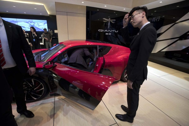 A sales person stand near the latest electric sports car from Chinese carmaker Qiantu displayed at the Auto Shanghai 2017 show at the National Exhibition and Convention Center in Shanghai, China, Wednesday, April 19, 2017. Models on display at Auto Shanghai 2017, the global industry's biggest marketing event of the year, reflect the conflict between Beijing's ambitions to promote environmentally friendly propulsion and Chinese consumers' love of hulking, fuel-hungry SUVs. (AP Photo/Ng Han Guan)