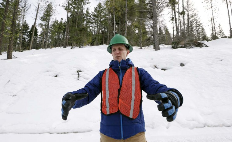 In this Feb. 22, 2017, photo, Ryan Haugo, senior forest ecologist for the Nature Conservancy, describes large trees being left while smaller ones are thinned on a 100-acre patch on private land they own overlooking Cle Elum Lake, in Cle Elum, Wash. As part of a broader plan by the nonprofit environmental group to restore the pine forests of the Central Cascades so they are more resilient to wildfires and climate change, they're cutting down trees to save the forest. (AP Photo/Elaine Thompson)