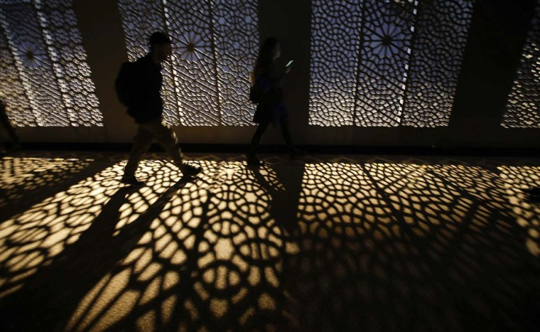 A visitor walks at the entrance of the 'Corian Cabana Club' interior design and decorative art exhibition, part of the Design Fair exhibition, in Milan, Italy, Thursday, April 6, 2017. (AP Photo/Luca Bruno)