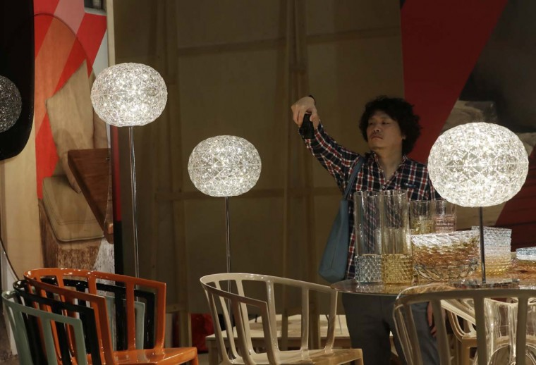 A woman looks at creations by Kartell's furniture designers, part of the Design Fair exhibition in Milan, Italy, Tuesday, April 4, 2017. (AP Photo/Antonio Calanni)