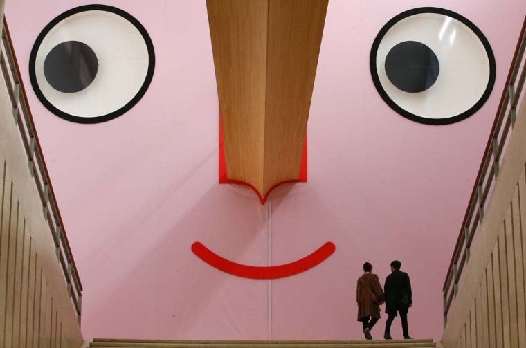 "People walk at the entrance of ""Giro Giro Tondo design for children"" exhibition, at the Triennale museum, in Milan, Italy, Monday, April 3, 2017. The Milan Design week is taking place in various locations across Milan from April 4 through 9, 2017. (AP Photo/Antonio Calanni)"