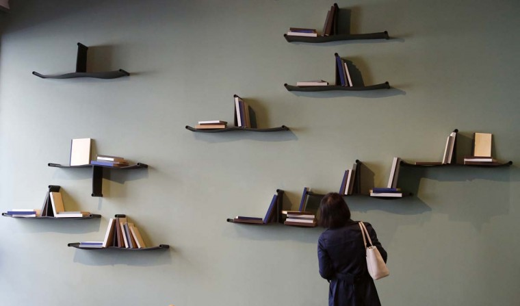 A woman looks at bookshelves, a creation by Cassina's furniture designers, part of the Design Fair exhibition, in Milan, Italy, Monday, April 3, 2017. (AP Photo/Antonio Calanni)