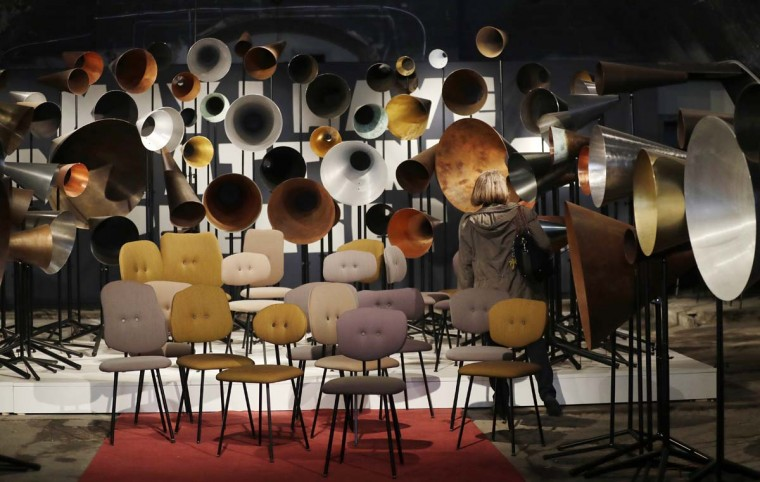 A woman looks creations by Maarten Baas' furniture designers, part of the Design Fair exhibition in Milan, Italy, Thursday, April 6, 2017. (AP Photo/Antonio Calanni)