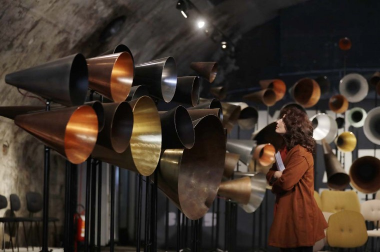 A woman looks at creations by Maarten Baas' furniture designers, part of the Design Fair exhibition in Milan, Italy, Thursday, April 6, 2017. (AP Photo/Antonio Calanni)