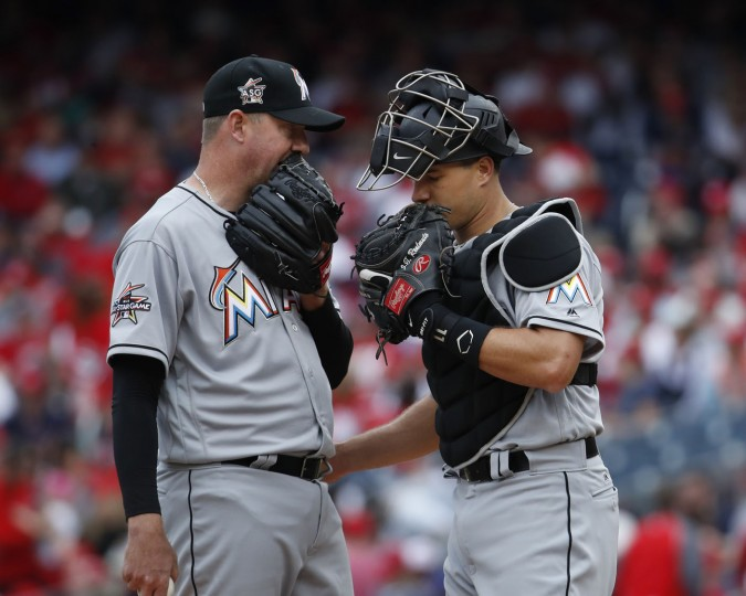 Miami Marlins catcher J.T. Realmuto, right, talks to teammate relief pitcher Brad Ziegler, left, after replacing Junichi Tazawa during the eighth inning of the opening day baseball game against the Washington Nationals Miami Marlins in Washington, Monday, April 3, 2017. Nationals won 4-2. (AP Photo/Manuel Balce Ceneta)