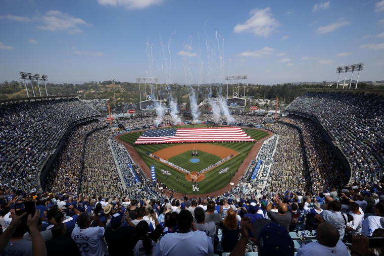 A giant American flag is unfurled on the field during the national anthem before the start of an opening day baseball game between the Los Angeles Dodgers and the San Diego Padres, Monday, April 3, 2017, in Los Angeles. (AP Photo/Ryan Kang)