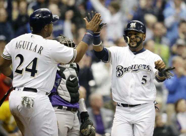Milwaukee Brewers' Jesus Aguilar (24) and Jonathan Villar score on a double by Eric Thames, not shown, against the Colorado Rockies during the fifth inning of an opening day baseball game Monday, April 3, 2017, in Milwaukee. (AP Photo/Jeffrey Phelps)
