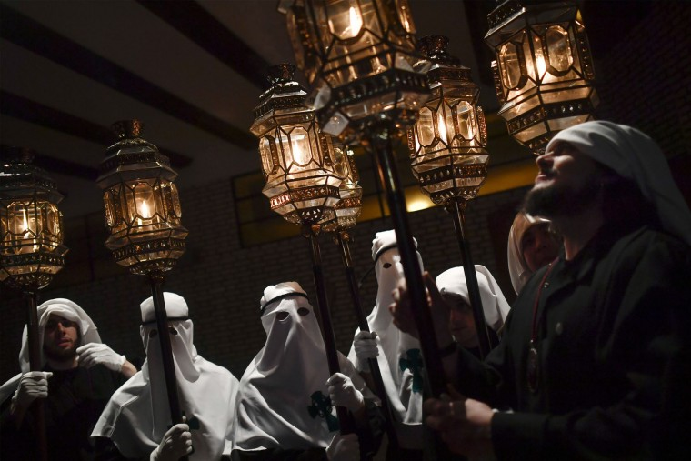 "Masked penitents stand beside light candles as they take part in the procession of the ""Santa Veracruz"" brotherhood, during the Holy Week in Calahorra, northern Spain, Wednesday, April 12, 2017. Hundreds of processions take place throughout Spain during the Easter Holy Week. (AP Photo/Alvaro Barrientos)"