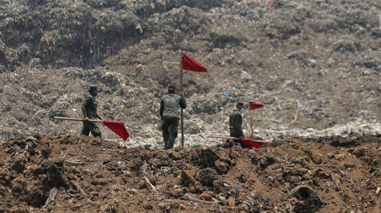 Sri Lankan army soldiers erect red flags to demarcate danger zones following the collapse of a garbage mound in Meetotamulla, on the outskirts of Colombo, Sri Lanka, Colombo, Sri Lanka, Monday, April 17, 2017. Rescuers on Monday were digging through heaps of mud and trash that collapsed onto a clutch of homes near a garbage dump outside Sri Lanka's capital, killing dozens and possibly burying dozens more. (AP Photo/Eranga Jayawardena)