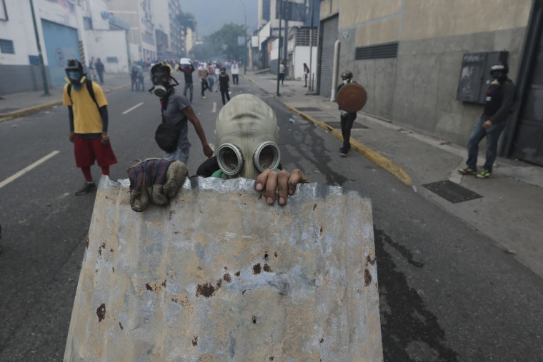 "A youth with a gas mask takes cover behind a piece of corrugated tin roofing during anti-government protests in Caracas, Venezuela, Wednesday, April 19, 2017. Tens of thousands of opponents of President Nicolas Maduro flooded the streets of Caracas in what's been dubbed the ""mother of all marches"" against the embattled president. (AP Photo/Fernando Llano)"