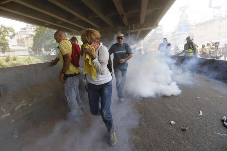 "Demonstrators run from tear gas and charging police officers during anti-government protests in Caracas, Venezuela, Wednesday, April 19, 2017. Tens of thousands of opponents of President Nicolas Maduro flooded the streets of Caracas in what's been dubbed the ""mother of all marches"" against the embattled president. (AP Photo/Ariana Cubillos)"