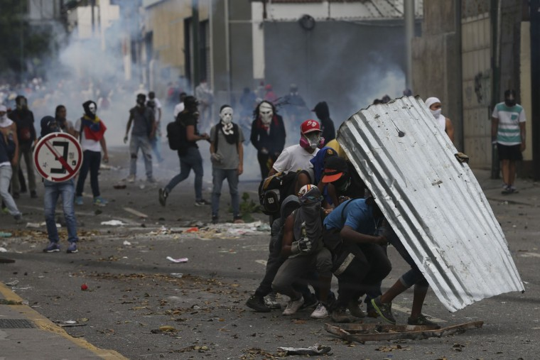 "Demonstrators take cover with a piece of corrugated tin roofing during anti-government protests in Caracas, Venezuela, Wednesday, April 19, 2017. Tens of thousands of opponents of President Nicolas Maduro flooded the streets of Caracas in what's been dubbed the ""mother of all marches"" against the embattled president. (AP Photo/Fernando Llano)"