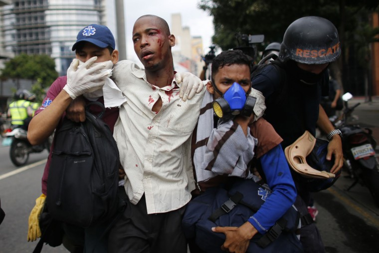 Paramedics assist a man injured during clashes with security forces during protests asking for the resignation of Presiden Nicolas Maduro in Caracas, Venezuela, Thursday, April 20, 2017. Tens of thousands of protesters flooded the streets again Thursday, one day after three people were killed and hundreds arrested in the biggest anti-government demonstrations in years. (AP Photo/Ariana Cubillos)
