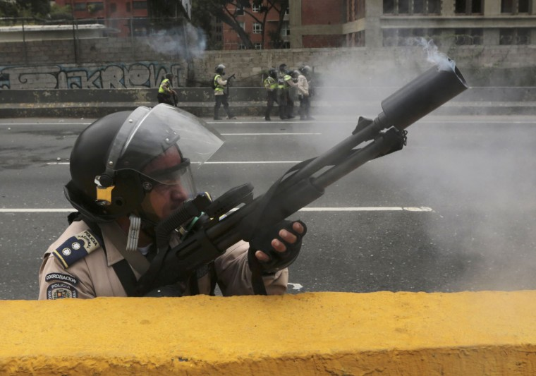 Smoke wafts from a police officer's tear gas launcher during clashes with opponents of President Nicolas Maduro in Caracas, Venezuela, Thursday, April 20, 2017. Tens of thousands of protesters flooded the streets again, one day after three people were killed and hundreds arrested in the biggest anti-government demonstrations in years. (AP Photo/Fernando Llano)