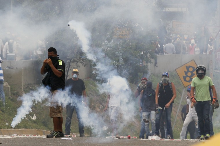 Opponents of President Nicolas Maduro stand amidst tear gas during clashes with security forces in Caracas, Venezuela, Thursday, April 20, 2017. Tens of thousands of protesters flooded the streets again Thursday, one day after three people were killed and hundreds arrested in the biggest anti-government demonstrations in years. (AP Photo/Ariana Cubillos)