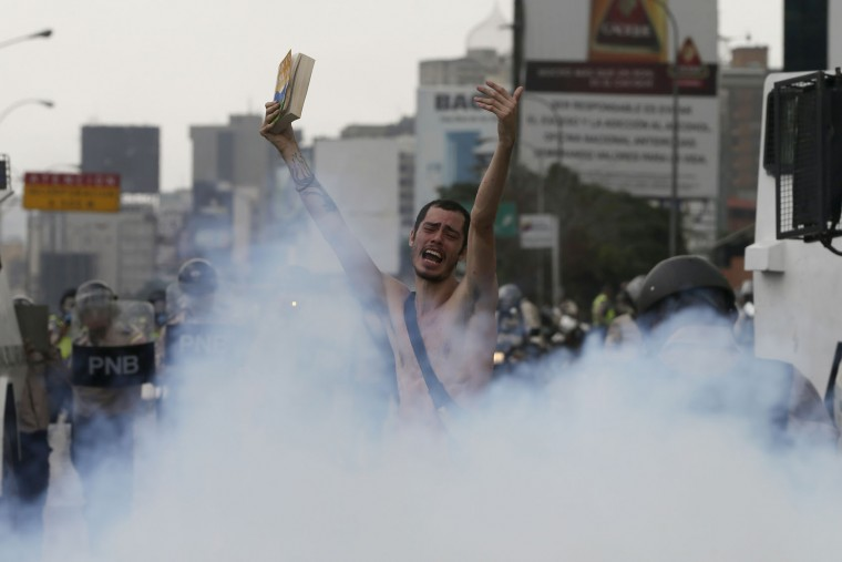 An anti-government protester holds a bible in the middle of a cloud of tear gas during a march in Caracas, Venezuela, Thursday, April 20, 2017. Tens of thousands of protesters flooded the streets again, one day after three people were killed and hundreds arrested in the biggest anti-government demonstrations in years. (AP Photo/Fernando Llano)