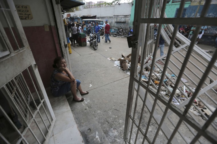 Shop owner Maria Gonzalez sits on the front stoop of her business, looted the night before, in El Valle neighborhood in Caracas, Venezuela, Friday, April 21, 2017. At least 12 people were killed overnight following looting and violence in Venezuela's capital amid a spiraling political crisis, authorities said Friday. Most of the deaths took place in El Valle, a working class neighborhood near Caracas' biggest military base where opposition leaders say a group of people were hit with an electrical current while trying to loot a bakery protected by an electric fence. (AP Photo/Fernando Llano)