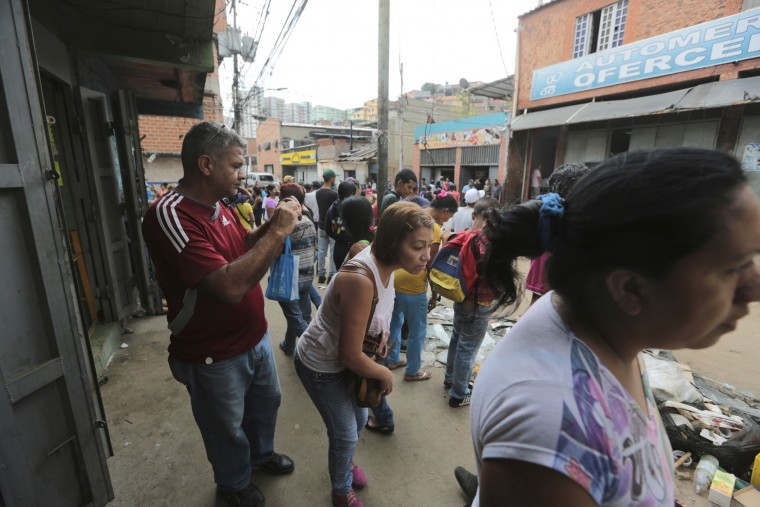 Pedestrians look at shops looted the night before, in the El Valle neighborhood in Caracas, Venezuela, Friday, April 21, 2017. At least 12 people were killed overnight following looting and violence in Venezuela's capital amid a spiraling political crisis, authorities said Friday. Most of the deaths took place in El Valle, a working class neighborhood near Caracas' biggest military base where opposition leaders say a group of people were hit with an electrical current while trying to loot a bakery protected by an electric fence. (AP Photo/Fernando Llano)