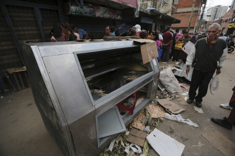 A pedestrian stands next to a refrigerator destroyed during looting the night before in the Valle neighborhood in Caracas, Venezuela, Friday, April 21, 2017. At least 12 people were killed overnight following looting and violence in Venezuela's capital amid a spiraling political crisis, authorities said Friday. Most of the deaths took place in El Valle, a working class neighborhood near Caracas' biggest military base where opposition leaders say a group of people were hit with an electrical current while trying to loot a bakery protected by an electric fence. (AP Photo/Fernando Llano)