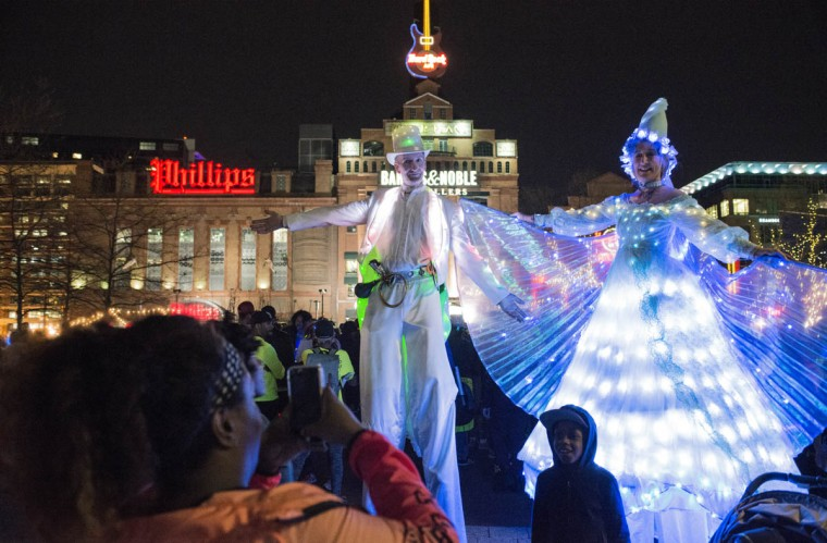 Strolling light giants from Big Whimsy pose for photos in the Inner Harbor at Light City Baltimore on Wednesday, April 5, 2017. (Emma Harris, Baltimore Sun)