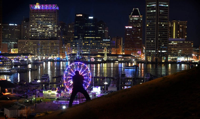 A photographer takes a picture of the Inner Harbor glowing from Light City Baltimore as it hosts a festival of lights, music and innovation March 31-April 8 2017. (Lloyd Fox/Baltimore Sun)