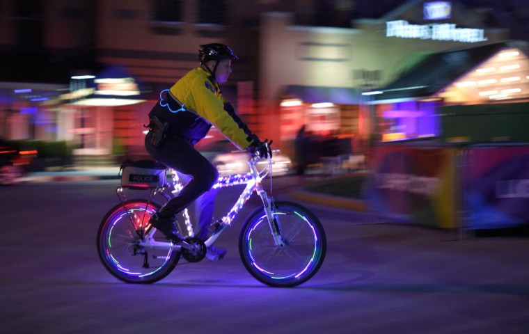 A Baltimore City Police Officer rides around the harbor with his bike decorated with lights. Light City Baltimore hosts a festival of lights, music and innovation March 31-April 8 2017. (Lloyd Fox, Baltimore Sun)