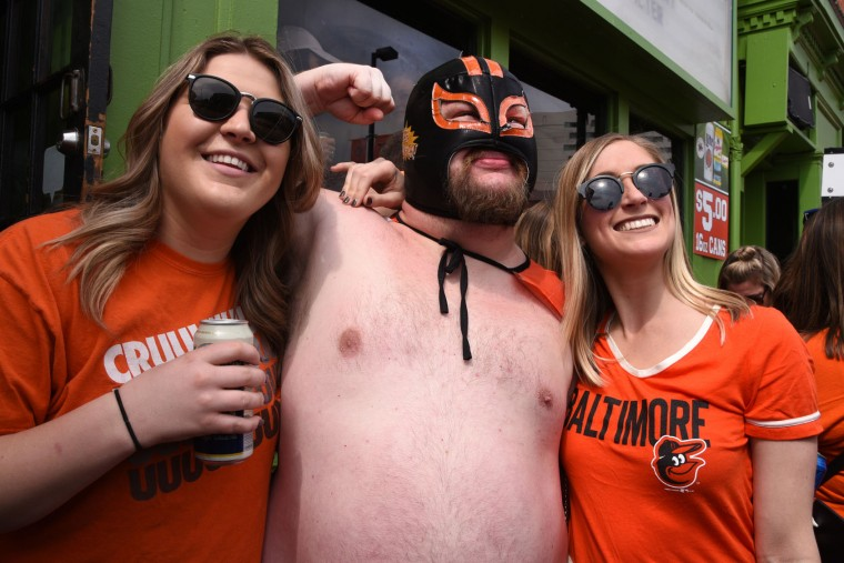Neal Moorhouse of Brooklyn Park, who calls himself Carne Cabeza (translation: Meathead), poses for a photo with Elizabeth McNaught, left, and Kaitlyn Gambino, right, both of Annapolis, outside Pickles Pub on the Orioles opening day for the 2017 season. (Amy Davis / The Baltimore Sun)