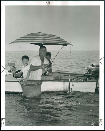 August 24, 1952-W.H. Bassell of Baltimore is shown sitting under his umbrella with two young companions. He hauls his boat to the Severn on a trailer every Sunday. He has a been a Sunday fisherman for 15-years. (Photo by Baltimore Sun Staff Photographer A. Aubrey Bodine)