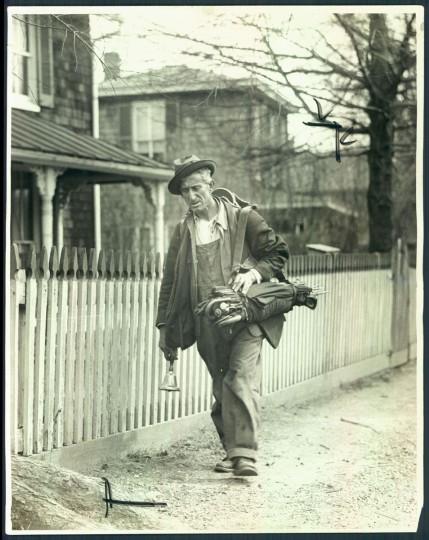 April 27, 1930-An umbrella mender walks along Rolling Road. (Photo by A. Aubrey Bodine/Baltimore Sun)