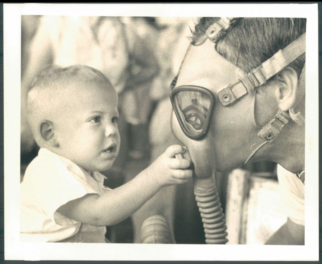Man wearing gas mask with child at Edgewood Arsenal. Photo dated June 29, 1958. (Baltimore Sun)