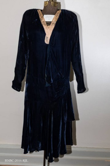Navy blue velvet wedding dress; lace trimmed at neckline; circular insert at bottom of front part of skirt. Worn by donor at wedding in St. James Church, Monkton in 1929. Gift of Mrs. Robert Pearce. (Photo from the Baltimore Historical Society via Enoch Pratt Library)