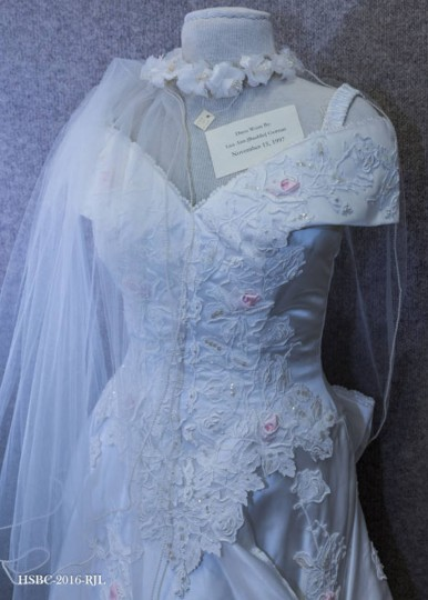 White, floor-length wedding gown with adornments of flower patterns, silk pink rose buds, and pearls; shoulder straps hold up the sleeves; in the back, there is a large bow, hiding the bottom of the zipper. Worn by Lisa Ann Baublitz, daughter of Carol Greensfelder Baublitz and Benjamin Baublitz, Jr., at her wedding to Brant Lee Geiman, on November 15, 1997. Gift of Carol Greensfelder Baublitz. (Photo from the Baltimore Historical Society via Enoch Pratt Library)