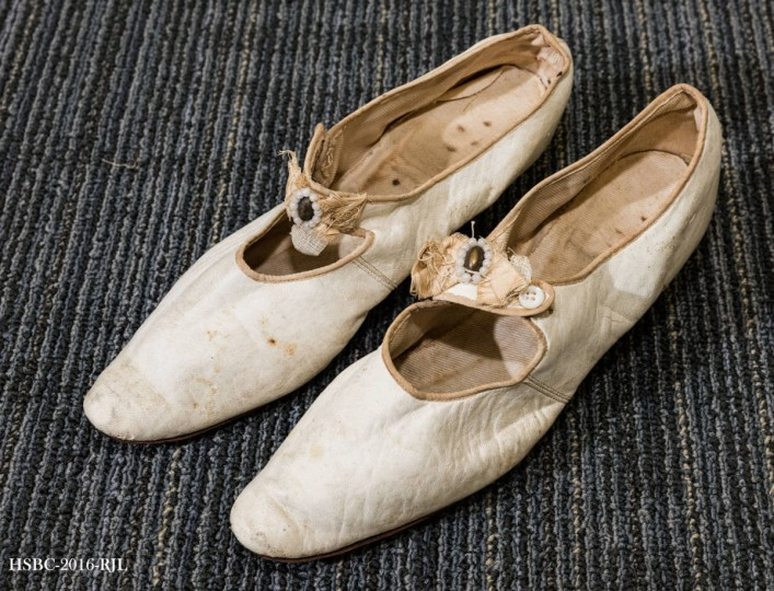 Woman's white/cream wedding shoes; leather uppers, fabric decorative bow with oval pearl decoration, short heel. Worn by Frank Drayer's mother in 1899. Gift of Mrs. B.S.L. Davis. (Photo from the Baltimore Historical Society via Enoch Pratt Library)