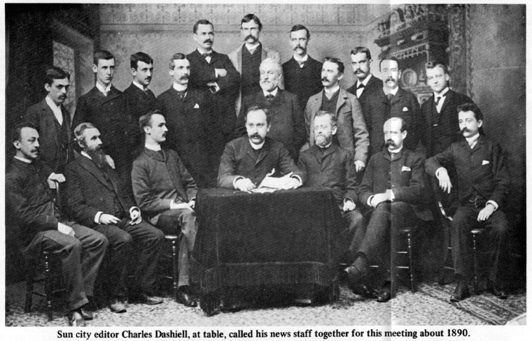 Baltimore Sun city editor, Charles Dashiell, at table, called his news staff together for this meeting in 1890.